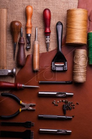 Photo for Manufacturing leather craft, iron metal buttons, sewing spools of threads and leather craft tools - Royalty Free Image