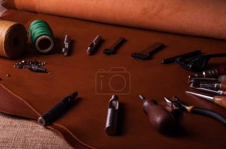 handmade manufacturing leather tools and threads on table in workshop