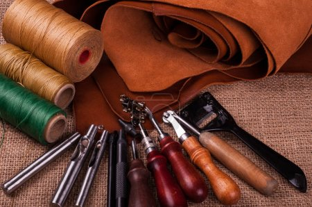 table with burlap surface, sewing spools of threads and leather craft tools