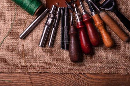 Photo pour Vue de dessus des outils artisanaux en cuir sur la surface de la toile - image libre de droit