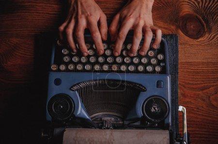 Photo pour Vue de dessus des mains masculines tapant sur la machine à écrire antique - image libre de droit