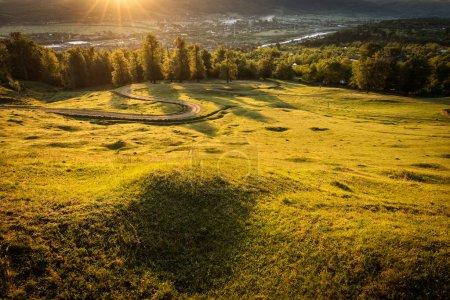 Photo pour Belle route de campagne courbée avec des sapins en arrière-plan au lever du soleil avec des rayons de lumière. Comanesti (Roumanie). - image libre de droit