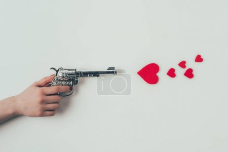 Photo for Cropped image of woman aiming gun at paper hearts on white, valentines day concept - Royalty Free Image