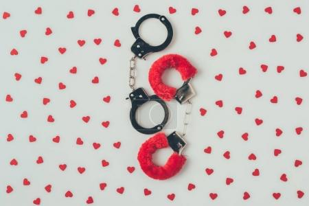 top view of black and red handcuffs with scattered paper hearts isolated on white