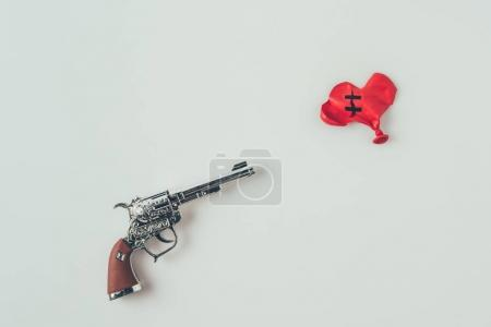top view of gun barrel aiming at repaired heart shaped balloon isolated on white, valentines day concept