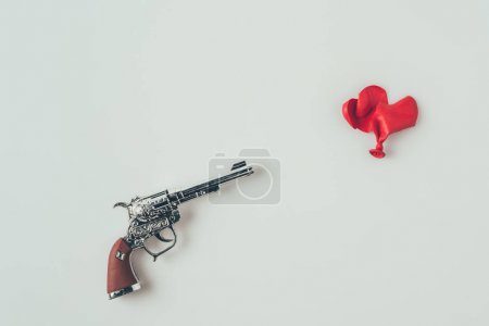 top view of gun barrel aiming at broken heart shaped balloon isolated on white, valentines day concept