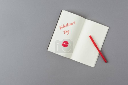 top view of open notebook with words valentines day and lips print on gray surface