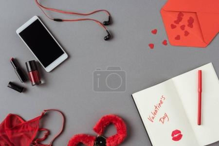 top view of smartphone, notebook with words valentines day on gray surface