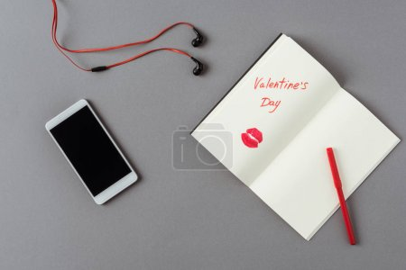 top view of smartphone and notebook with words valentines day on gray surface