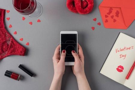 cropped image of woman holding smartphone in hands, notebook with words valentines day