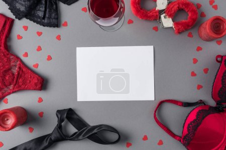 top view of white sheet of paper between underwear and glass of wine