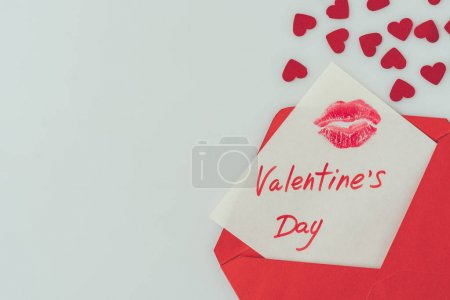 top view of happy valentines day postcard with lips print in envelope isolated on white