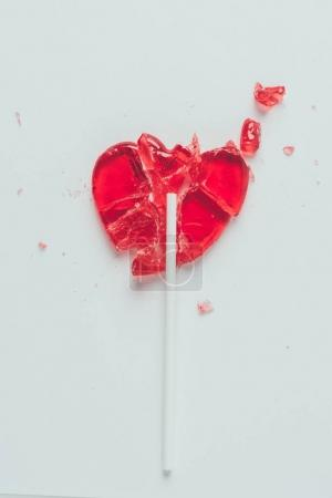 top view of broken heart shaped lollipop isolated on white, valentines day concept