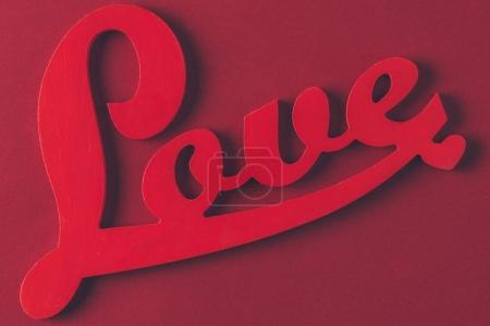 top view of red sign with word love isolated on burgundy