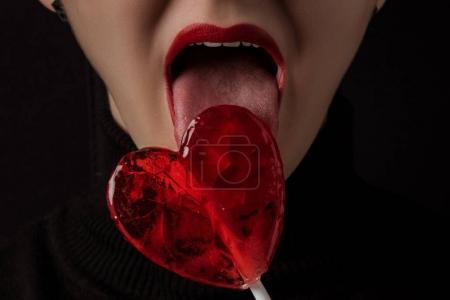 Photo pour Cropped image of woman licking heart shaped lollipop isolated on black, valentines day concept - image libre de droit