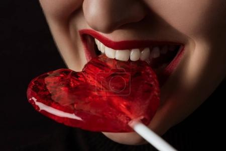 Photo for Cropped image of woman biting heart shaped lollipop isolated on black, valentines day concept - Royalty Free Image
