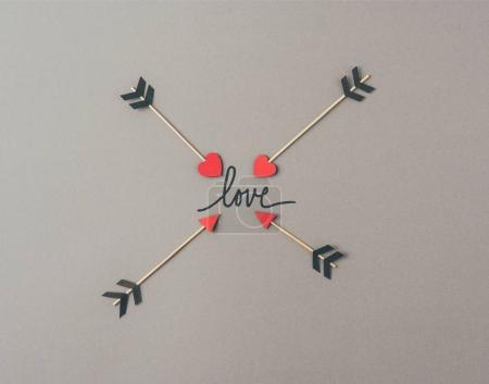 Photo for Top view of four arrows and word love on gray surface - Royalty Free Image