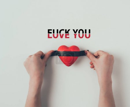 Cropped image of woman putting insulating tape on red heart with words love you fuck you on white