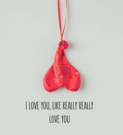 Top view of deflated balloon on ribbon with text i love you like really really love you isolated on white