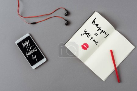 Top view of smartphone with words happy valentines day and notebook with lips print on gray surface