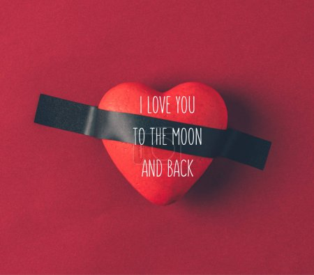 top view of red heart under insulating tape with words i love you to the moon and back on red