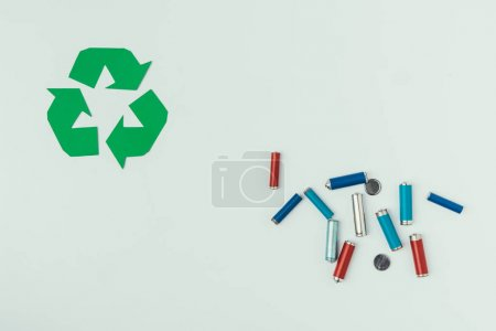 top view of recycle sign and various types of batteries isolated on grey