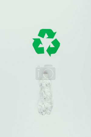 top view of recycle sign and plastic bottle isolated on grey