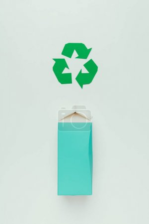 top view of recycle sign and cardboard package isolated on grey
