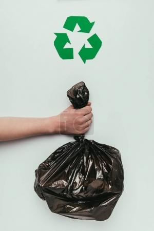 cropped shot of woman holding garbage bag in hand with recycle sign isolated on grey
