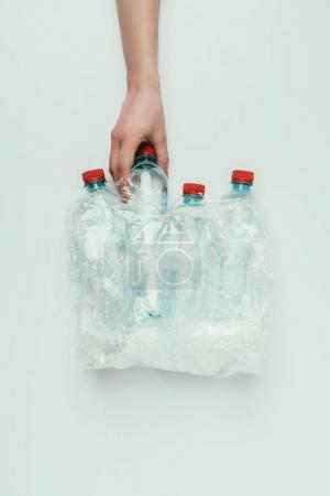 Photo pour Vue partielle de la femme prenant une bouteille en plastique du sac en plastique isolé sur gris - image libre de droit