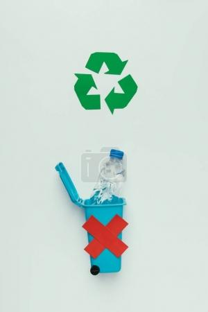 top view of recycle sign, trash bin with red cross and plastic bottle isolated on grey, recycling concept