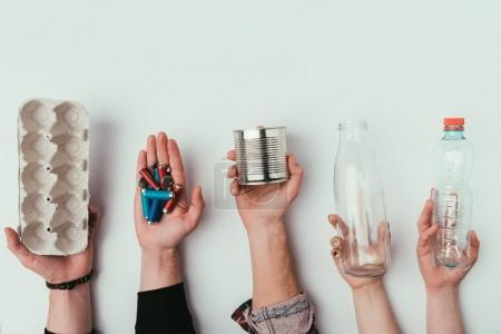 partial view of group of people holding various types of garbage isolated on grey