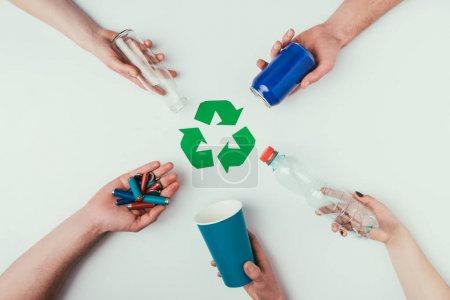 partial view of people showing various types of garbage around recycle sign isolated on grey