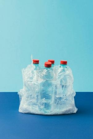 Photo for Close up view of plastic bottles in plastic bag on blue background, recycle concept - Royalty Free Image