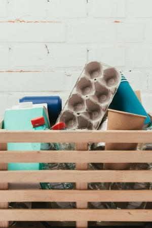 close up view of various types of trash in wooden box with white brick wall on background