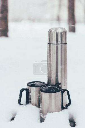 close up view of thermocups and thermos in snow in winter forest