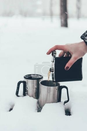 partial view of woman pouring coffee into cups in snow in winter