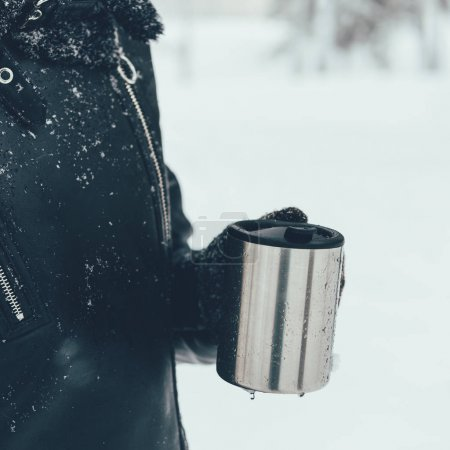 Photo for Partial view of woman holding thermocup with hot drink on winter day - Royalty Free Image
