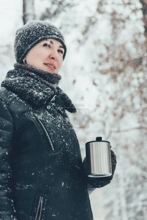 portrait of smiling woman with thermocup with hot drink looking away on street i winter