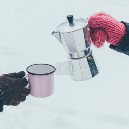 cropped shot of couple holding cup and coffee maker in hands on winter day