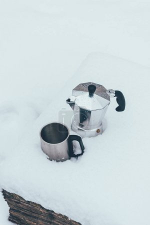 close up view of cup and coffee maker in snow