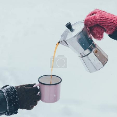 Photo for Partial view of man pouring hot coffee into cup on winter day - Royalty Free Image