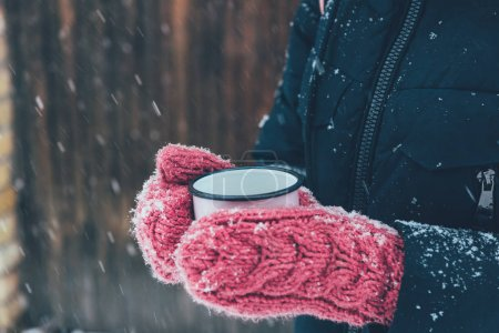 Photo for Cropped shot of woman holding cup of tea in hands on winter day - Royalty Free Image