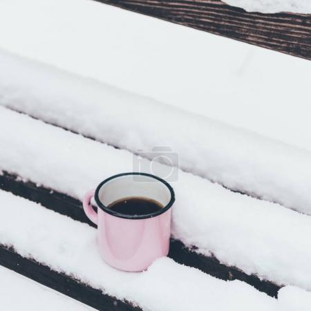 close up view of cup of coffee on wooden bench on snowy day