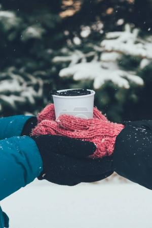 partial view of couple holding thermocup with hot drink together in winter forest