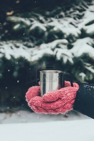 cropped shot of woman holding cup of tea in hands on winter day