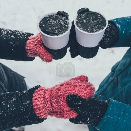 Photo for Partial view of couple with hot drinks holding hands on street in winter - Royalty Free Image