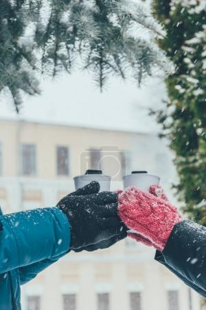cropped shot of couple holding thermocups with hot drinks on street in winter