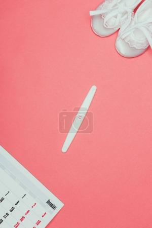 top view of childish shoes, pregnancy test and calendar isolated on pink