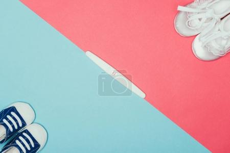top view of arrangement of  childish shoes and pregnancy test